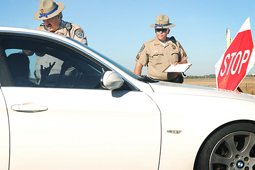 California Highway Patrol Officer Dave Gaskins, left, checks for drivers licenses as Srgt. Kevin Duncan, right, look on during their four hour DUI road check point operation on eastbound Highway 12 Sunday afternoon.