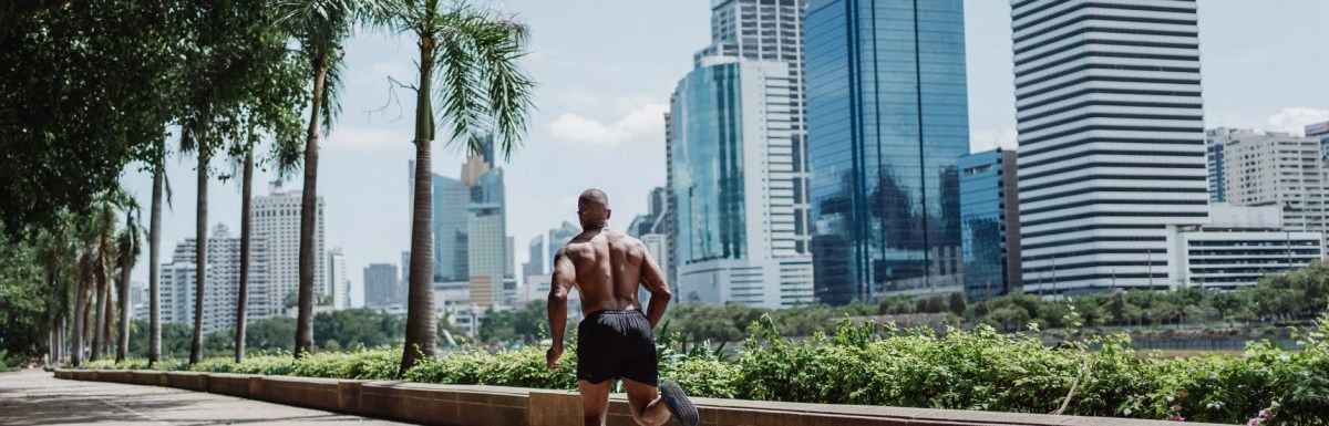 back view of a shirtless man running on concrete walkway