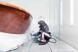 Stefan Baumgart in Schutzkleidung bei Holzlackierarbeiten in der Lackierkabine der Bootswerft Baumgart in Dortmund