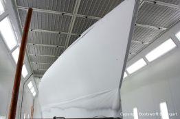 Der Rumpf der Comfortina 38 Segelyacht ist jetzt weiss grundiert in der Lackierkabine der Bootswerft Baumgart in Dortmund