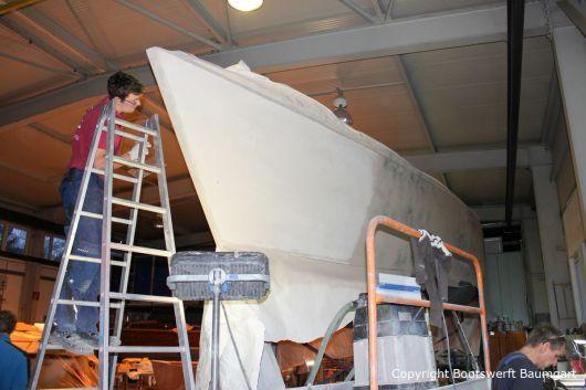 Kleine Unebenheiten am Rumpf der Comfortina 38 Segelyacht werden beseitigt. Stefan Baumgart bei den Arbeiten in der Werfthalle der Bootswerft Baumgart in Dortmund