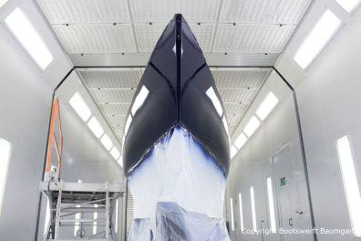 Erste Lackschicht in dunkelblau auf der Comfortina 38 Segelyacht. Bugansicht in der Lackierkabine der Bootswerft Baumgart in Dortmund