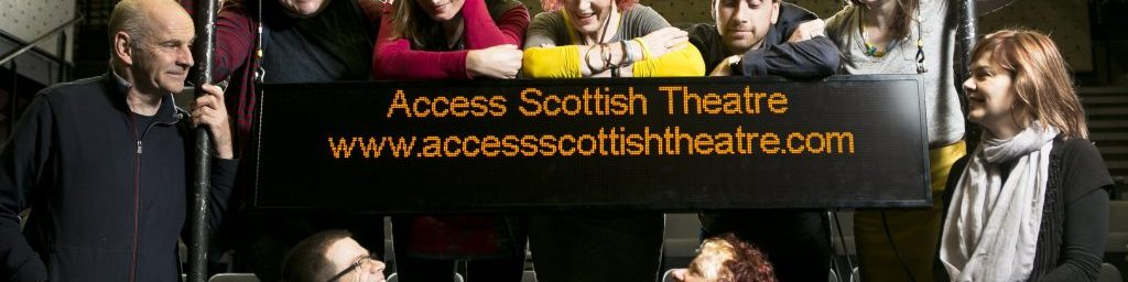 A group of people gathered on a stage with the seating bank behind them. They are gathered around a captioning unit that says 'Access Scottish Theatre. www.accessscottishtheatre.com