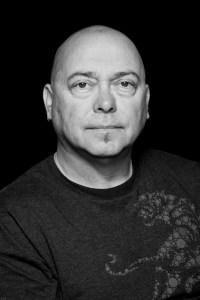 A black and white photo of Garry Robson. He has a round face, no hair and a small black goatee.