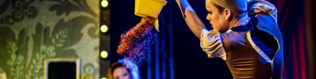 A man in a dress and a hairnet pours out a big tub of glitter.