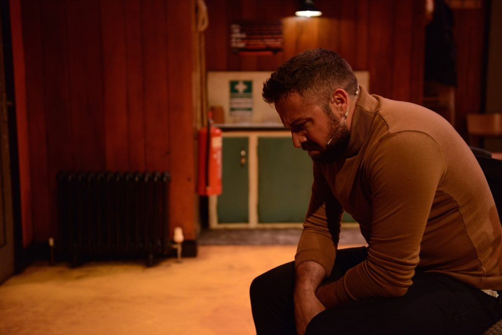 An actor in a brown jumper sits hunched over on stage. He appears upset.