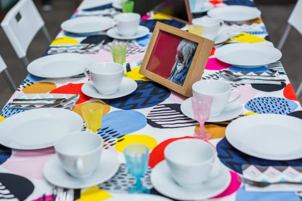 A collection of white cups and saucers on a bright patterned tablecloth.