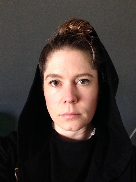 Bryony is a woman in her 30s with her hair tied back and wearing a black hoodie with the hood up. She stares intently at the camera.