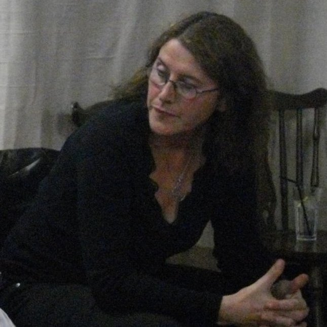 Aine is a white middle aged woman with long brown hair and glasses. In this picture she is perched on the edge of a chair her hands clasped together, while she concentrates on something to the side.