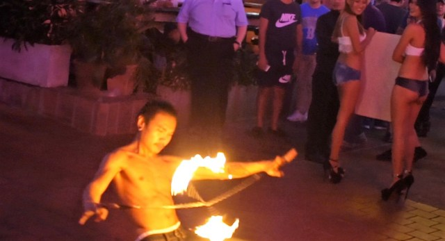 A street performer in Bangkok red light district juggles fire sticks while two sex workers turn and smile Photo Credit: Borderless News Online