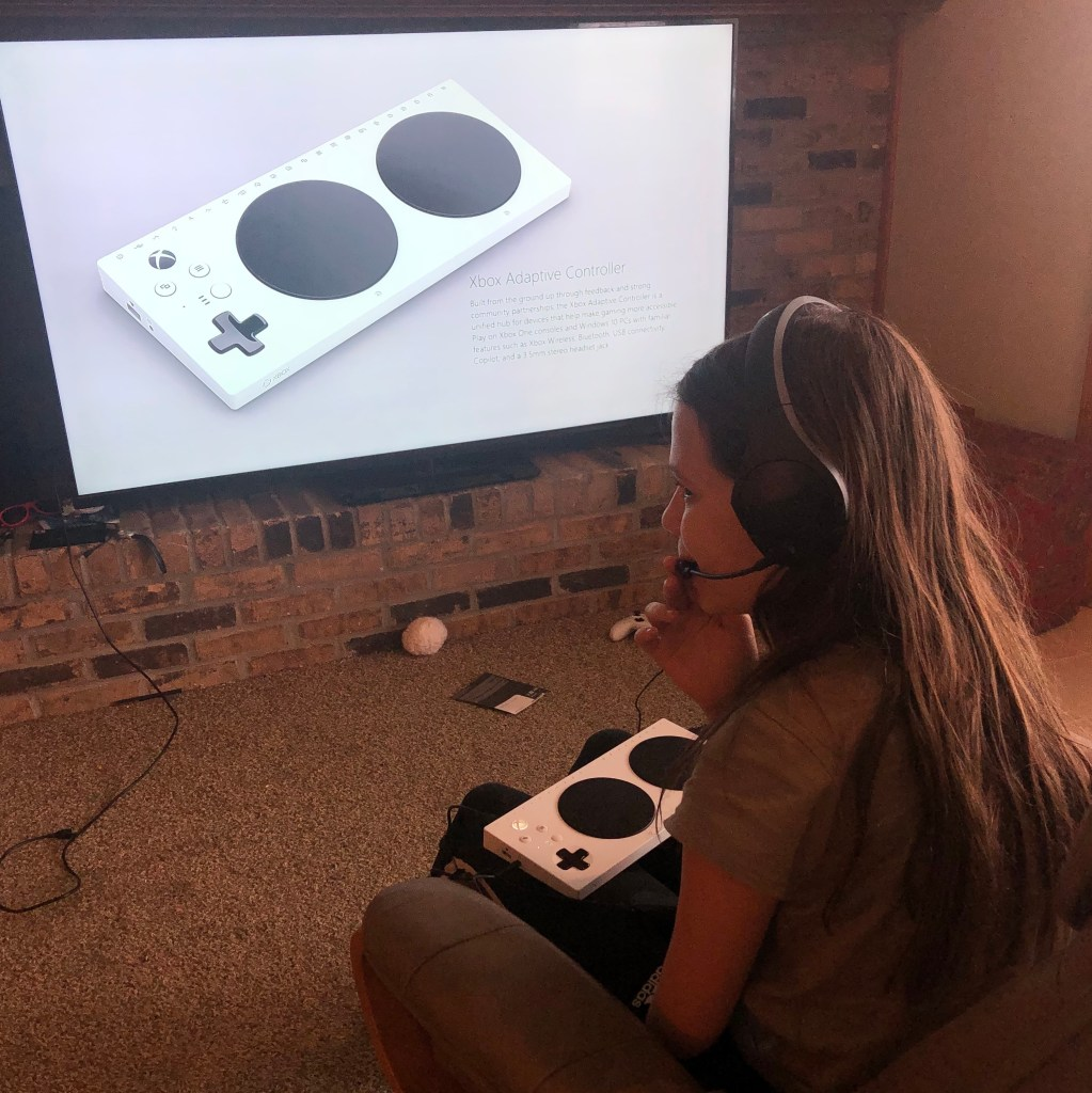 Jordan wears an Xbox headset with an Xbox adaptive controller on her lap. You can see the same controller in the background on a very large TV screen.