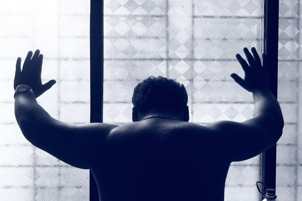 Depressed Man leaning on translucent wall - view from back