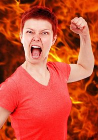 Angry woman raising fist in front of flame background