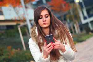 teen girl absorbed in smartphone