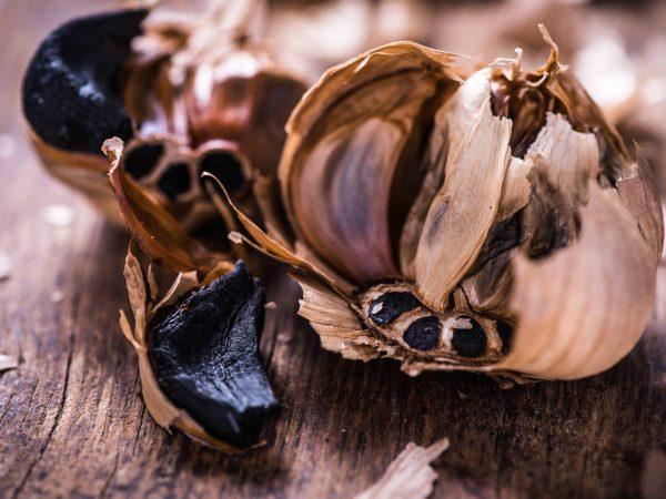 Whole balsamic black garlic on wooden board
