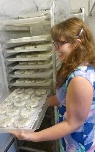 Andrea Davis checks trays of her Dark Moon goat cheese rounds at Broken Shovels Farm.