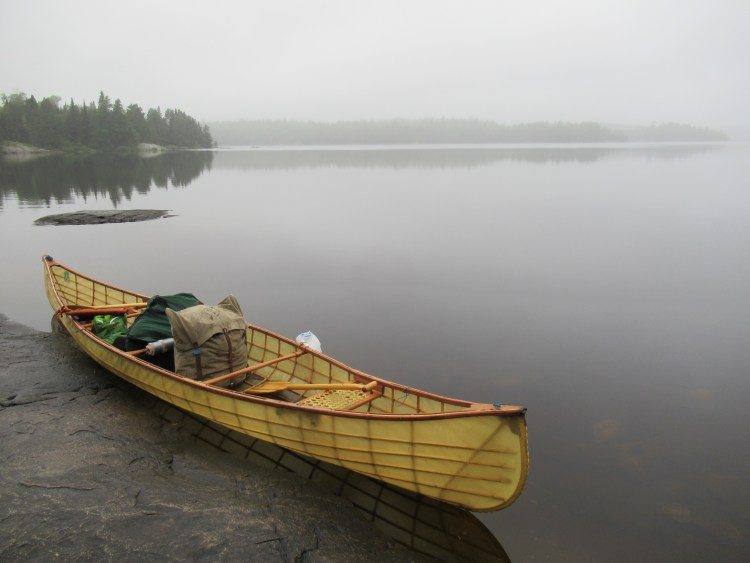 A canoe with two Duluth bags in it next to the lake in the Boundary Waters Canoe Area (BWCA)