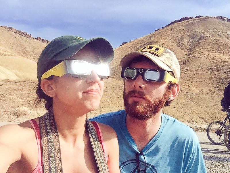Nick and Angelina wearing solar eclipse glasses in the painted hills of Oregon. Boundless-Journey.