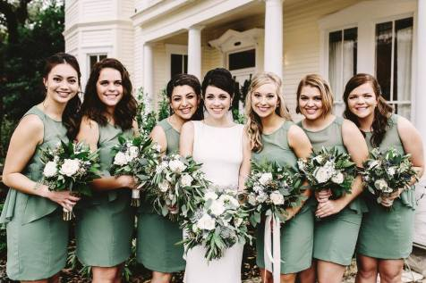 Bride and bridesmaids with winter bouquets of white flowers.