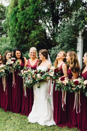 Lush bridal bouquet of mixed greenery and bold marsala blooms.