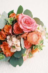 Coral rose, orange ranunculi and peach stock in a traditional design for a bride.