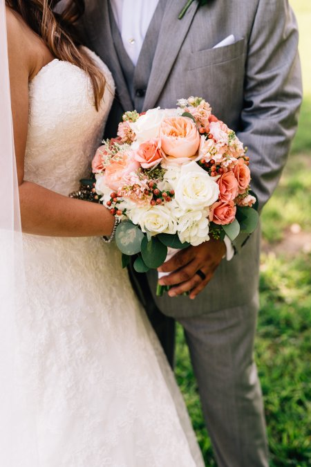 Bridal bouquet of juliette garden roses, ivory roses and coral spray rose for a bride.