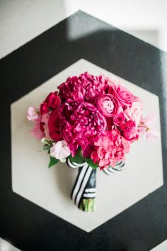 Bouquet of hot pink peony, roses and ranunucla with black and white stripe ribbon details.
