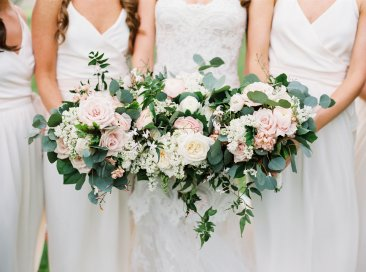 Bride and bridesmaids with mostly blush bouquets with lush foliages.