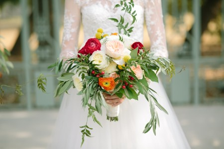 Casual summer bouquet of pastel blooms and red and orange ranunucls.
