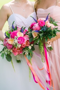 Cascading ribbons on bride and bridesmaids bouquets of coral peony, garden roses and ranunucla.