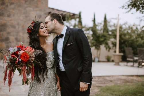 Bride with lush, rich shades of red and wearing a flower crown.