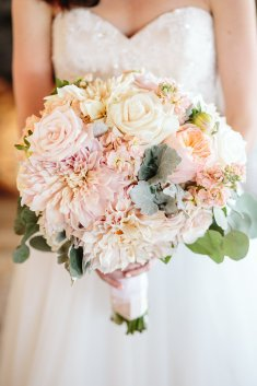 Pastel bridal bouquet featuring dahlia, stock, and roses in peach and blush.