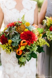 Bright colorful bridal bouquet with orange red and yellow flowers including succulents.