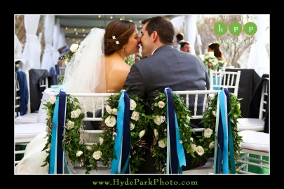 Bride and groom chair details- fresh foliage garland and flowers with shades of blue ribbons.