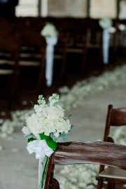 Aisle lined with fragrant petals and bundles of white stock and roses.