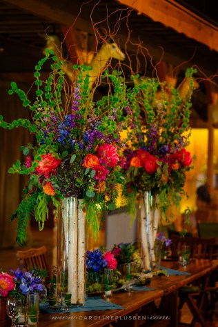 Tall, elevated centerpieces for wedding party table.