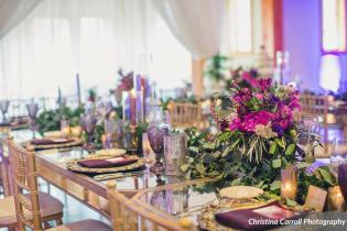 Head table with taper candles,garlands and jewel tone flowers