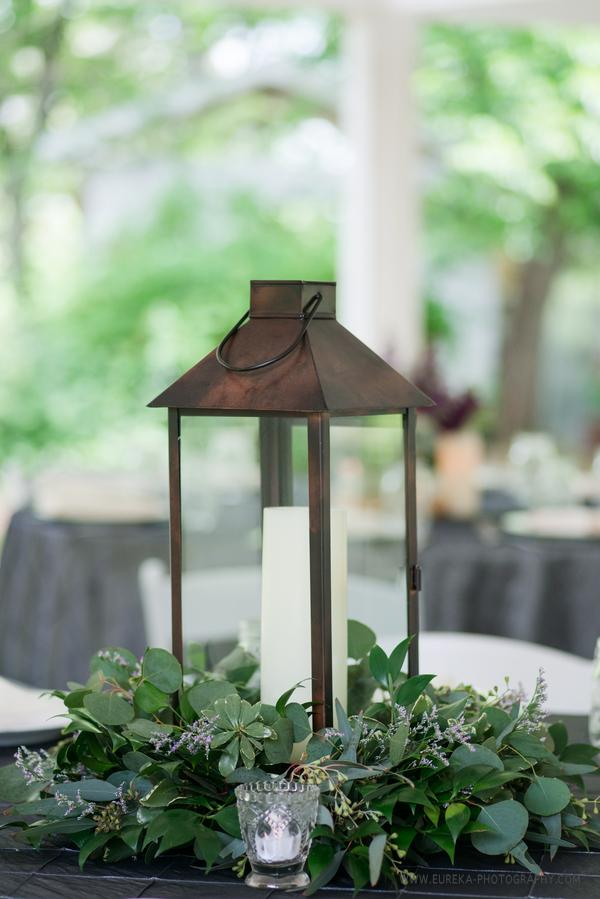 Centerpiece with lanterns and greenery bouquets of austin