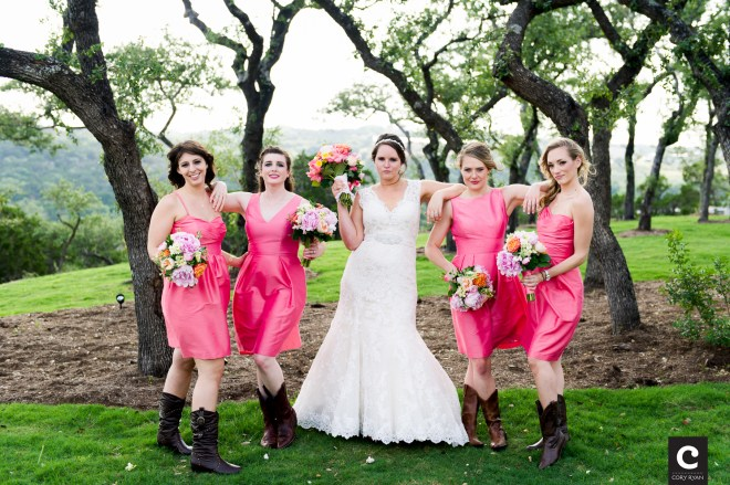 Bridesmaids wearing cowboy boots and colorful wedding flowers.