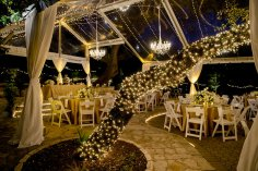 Clear tent with twinkle lights and chandeliers for wedding reception.