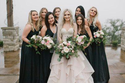 Bride in blush wedding gown, bridesmaids in black gowns.