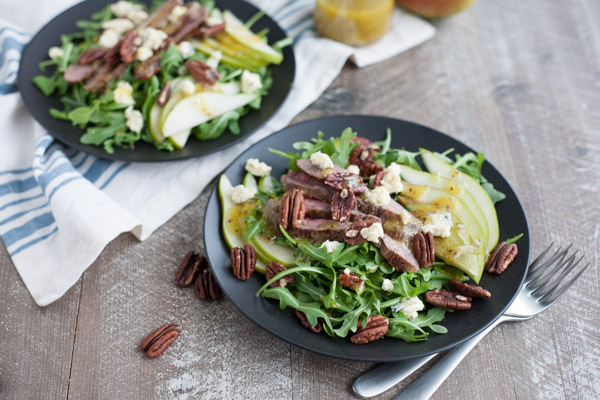 Arugula Flank Steak Salad with Pears and Blue Cheese | BourbonandHoney.com -- Filling, savory and delicious, this Flank Steak Salad recipe is topped with fresh pears, toasted pecans and lots of blue cheese and perfect for lunch or dinner!