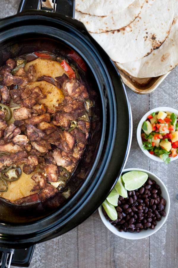 Slow Cooker Jamaican Jerk Chicken Tacos | BourbonandHoney.com -- Spicy, sweet and super flavorful, these Slow Cooker Jamaican Jerk Chicken Tacos are an easy make ahead dinner that can serve a crowd!