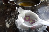 Lining strainer with butter to strain clarified butter