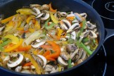 Peppers, onions, and mushrooms in a pan