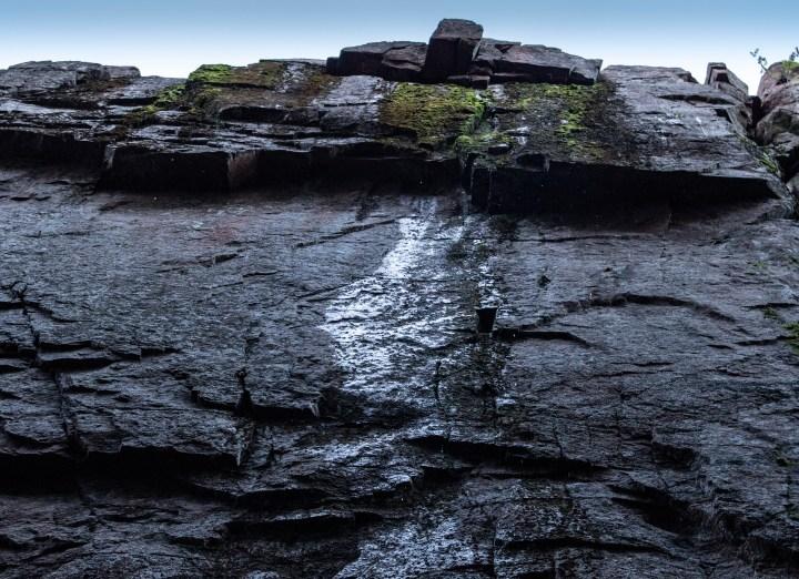 Från Slåttdalsskrevans bergsväggar droppar vattnen.