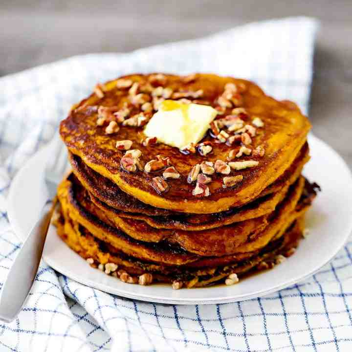 A plate with pumpkin pancakes sprinkled with pecans and a tab of butter.
