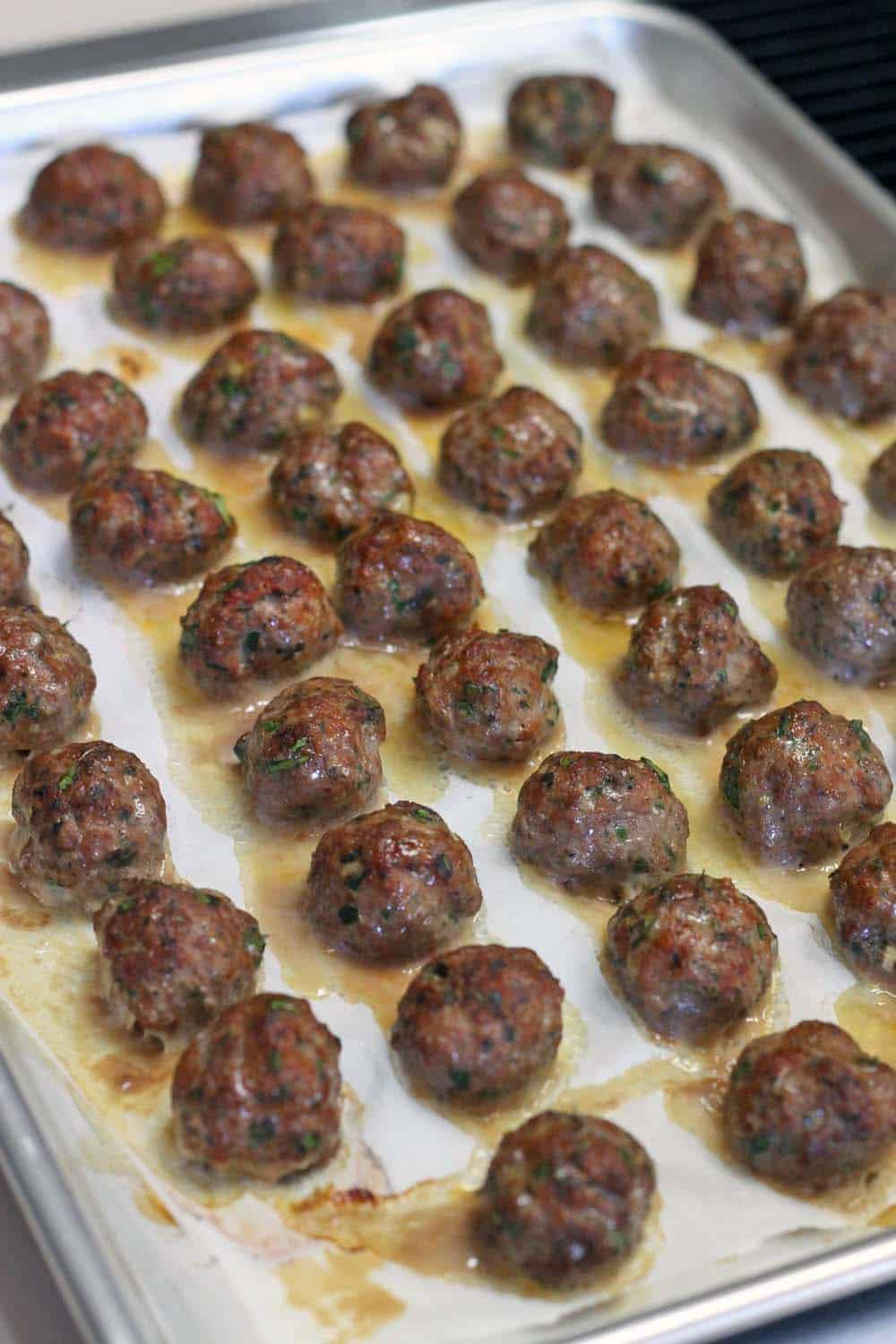 This Paleo/Whole30 baked version of Greek Meatballs (Keftedes) are paired with a super easy Romesco Sauce. The PERFECT make-ahead appetizer for your next party!