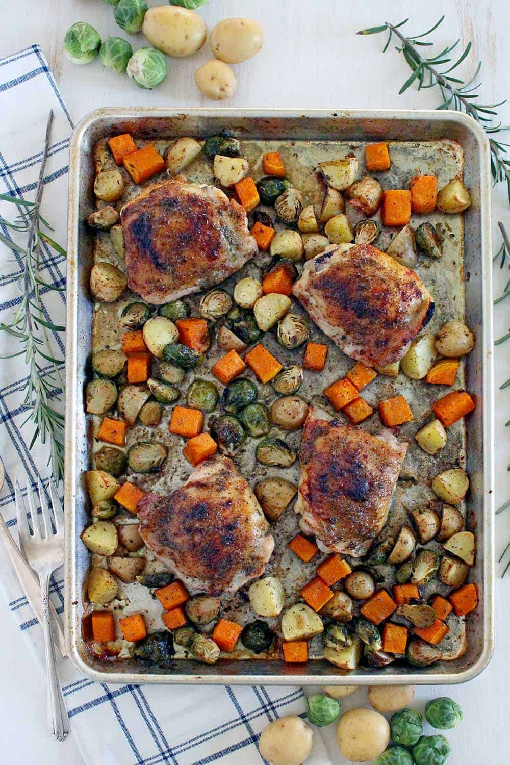 This Maple and Rosemary Glazed Chicken and Fall Veggies Sheet Pan Dinner is an easy way to make a full meal in one pan! Slightly sweet and savory at once, the flavor of the glaze is amazing and coats every single bite. The whole family will love this. #sheetpandinner #paleo #brusselssprouts