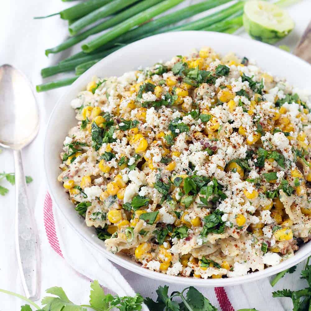 This Mexican Street Corn Pasta Salad is PACKED with sweet corn and tossed in a creamy chili lime dressing. With plenty of queso fresco, bacon, jalapeño, and green onions, this flavor-packed recipe is perfect for a potluck! Can be made with frozen, fresh, or canned corn. Plus, no grilling required! For extra smoky and charred flavor without grilling, the corn is sautéed in bacon fat.